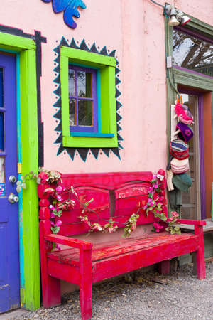 vintage furniture: Antique Wooden Bench Outside of a Colorful Shop in Madrid, NM Editorial