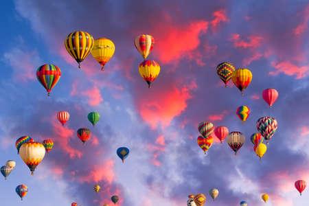 Kleurrijke heteluchtballonnen tijdens de vlucht verlicht door de vroege ochtend licht
