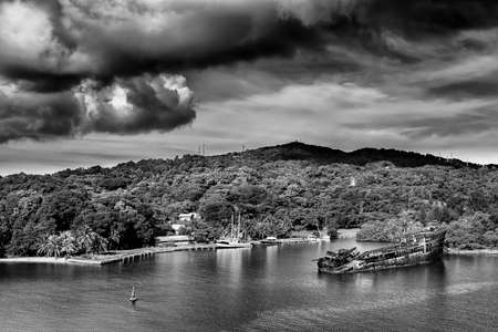 sunken boat: Old whipwrecked vessel under an ominous sky off the coast of Roatan, Honduras Stock Photo