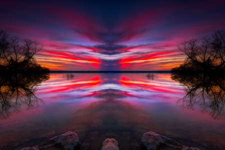 Vivid Texas winter sunset over an urban lake with applied photoeffects to enhance symmetry Stock fotó