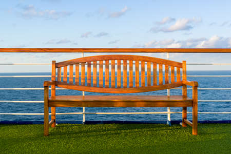 caribbean cruise: Wooden bench bathed in golden early morning light on the top deck of a Caribbean cruise ship Stock Photo
