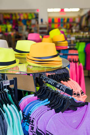 clothing shop: Festive, colorful hats and t-shirts on display inside a waterfront clothing shop in Belize Stock Photo