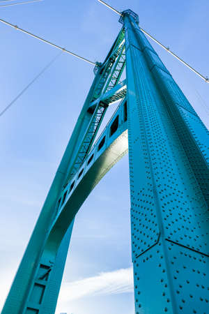 Base view of one of the aqua colored suspension towers of Lion's Gate Bridge in Vancouver, BC, Canada on a sunny morning 版權商用圖片