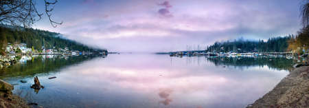 winter sunrise: Foggy sunrise at Panorama Point in Vancouver, BC featuring a calm ocean with sunrise reflections on the smooth water Stock Photo