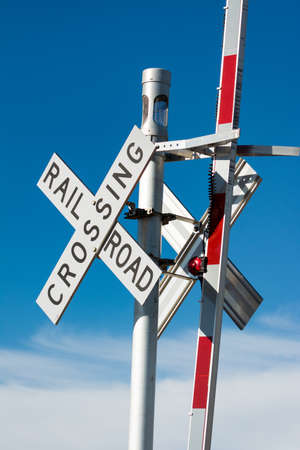railroad crossing: Railroad crossing sign against a blue sky