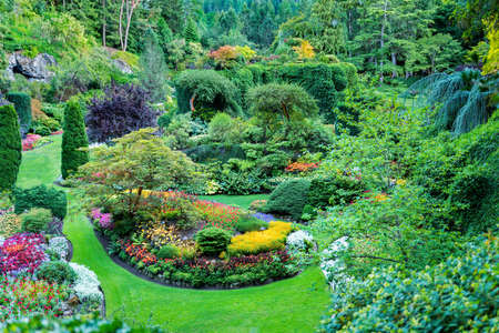 Lush, ornate Canadian gardens featuruing well-manicured flower beds, bushes, and trees Standard-Bild