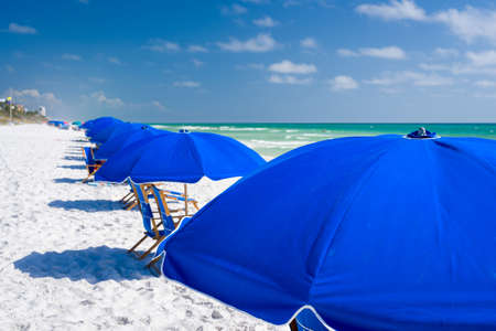 Group of blue beach umbrellas arranged in a row on a sunny day on one of Floridas Emerald Coast white sand beaches