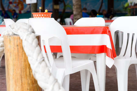 Outdoor cafe table draped with a orange striped vinyl tablecloth in Cozumel, Mexico Reklamní fotografie