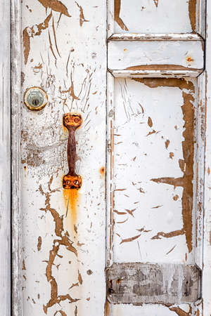 building exteriors: Peeling, weathered door and rusted handle in a poor Mexican neighborhood