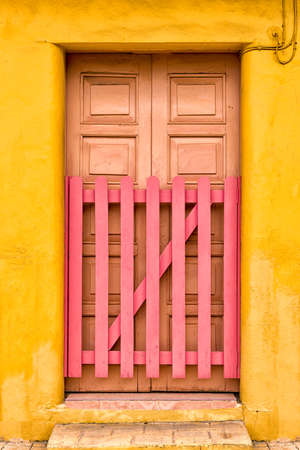Multicolored adobe building and wooden door with picket gate in Cozumel, Mexico