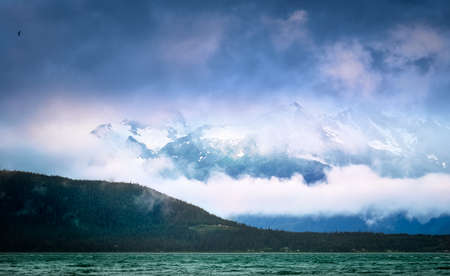 Clouds and fog covering the snow-capped mountain peaks over the inlet at Skagway, Alaska