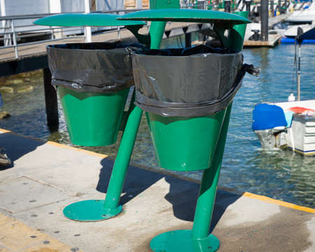 Two green trash cans lined with trash bags mounted on a pier in Cabo San Lucas, Mexico Stock Photo
