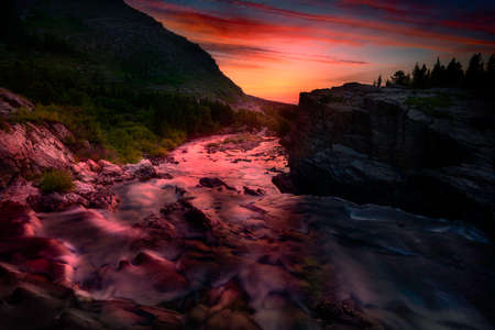 Colorful sunrise over the rapids of Swiftcurrent Creek in Glacier National Park, Montana
