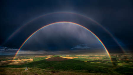 Photographer capturing a stunning double rainbow over the Palouse hills