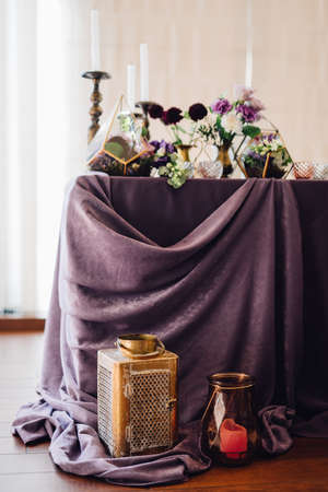 Festive table decorated by violet cloth, flowers and greenery, candles on candleholders with golden lantern and candles near them. Wedding decor