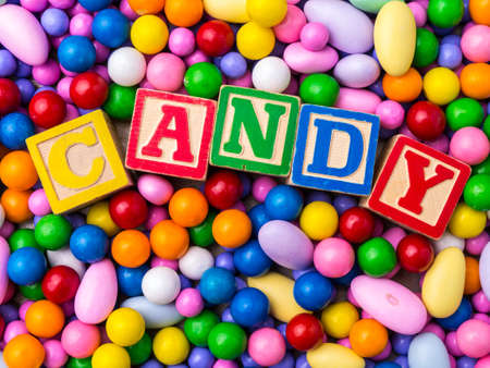 Candy spelled out in alphabet blocks with colorful candy background Stock fotó