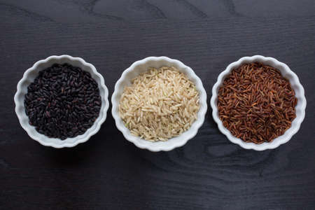 Black, white and red rice in bowls.