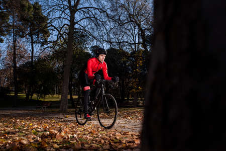 cyclist riding in the park with leaves on the ground in autumn 03 스톡 콘텐츠