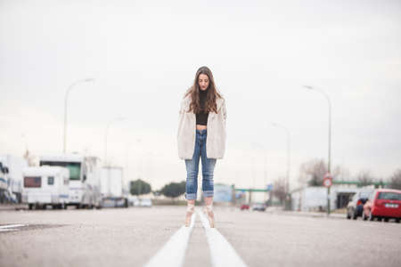 woman dancer on ballet tips, jeans and white coat on the street and look down