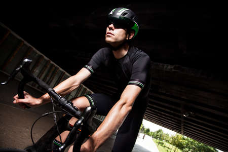 cyclist on black in to the tunnel with helmet and bike