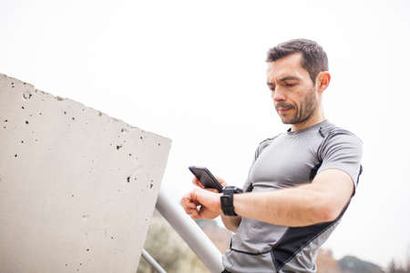 runner synchronizing his watch and smart phone