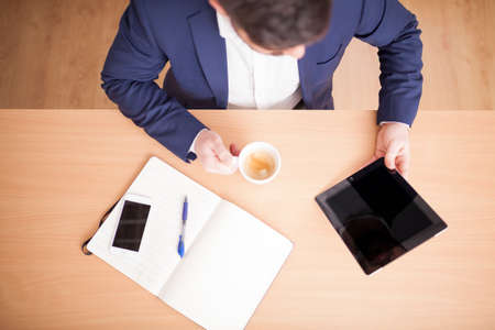businessman in suit in meeting room with tablet and coffee aerial view