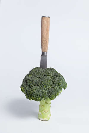 broccoli on white background with knife with bamboo handle nailed Imagens