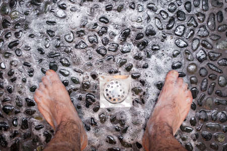 View of a mans feet while taking a shower copper floor of black stones Imagens