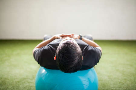 man training with training ball on artificial grass