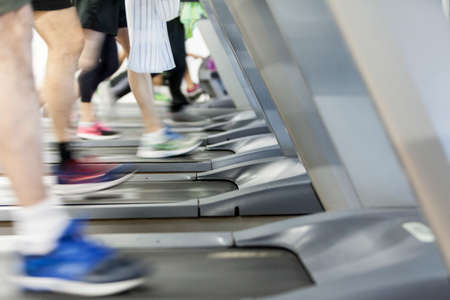 image of several treadmills with people and with sneakers of various colors