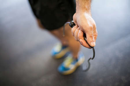close-up of mans hand near the cage jumping rope
