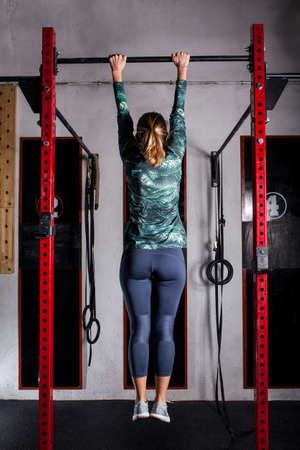 Woman doing pull-ups in cross fit box Imagens
