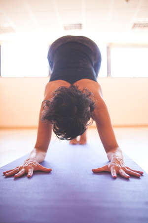 yogi crushes on arms and feet upside down, view of hands