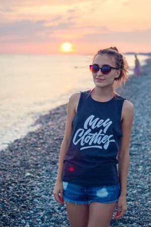 Sunset dawn. Young woman standing on a rounded pebble stones. The girl enjoys the unusual beach, pebbles on the shore of the Black sea