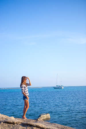 Young girl on blue sea background. Tropical country. Yacht on the background