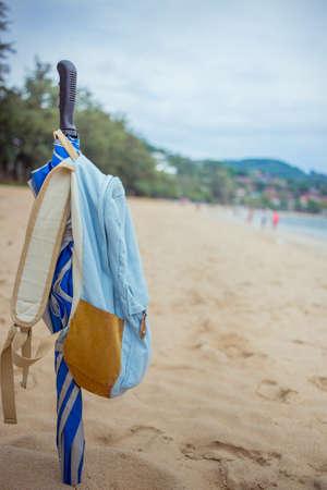 Folded umbrella stuck in the sand. The umbrella weighs backpack. Beach, Sea, Thailand Kata. Tropics