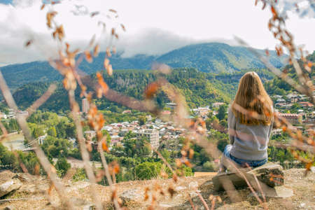 So a beautiful woman is standing on top of a mountain in a hoodie. looking at the mountains and trees from above.Beautiful panorama. Borjomi. Far away city. On top of the mountains and clouds
