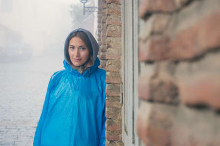 Young fashion woman in blue raincoat standing in mist outdoors. Brick wall of the old house. Pavers. A drizzle of rain. Gloomy atmosphere