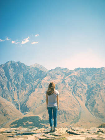 A young girl stands on the edge of a cliff. Mountain in the background. Soldiers stand. Blue sky. Young in jeans and a t-shirt
