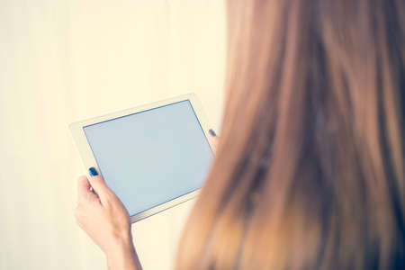 Girl on a tablet computer, browses the information. The white background and the screen.