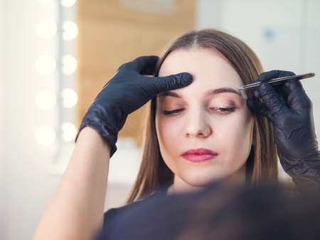 Master makeup corrects, and gives shape to pull out with forceps previously painted with henna eyebrows in a beauty salon. Professional care for face. Stock Photo