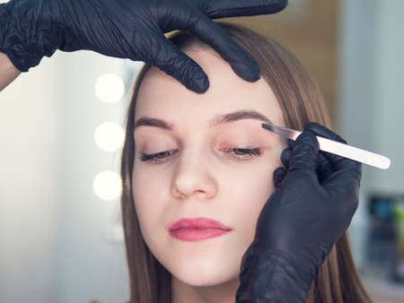 Artistic design of eyebrows. Correction. Pin forceps Make up artist doing professional make up of young woman