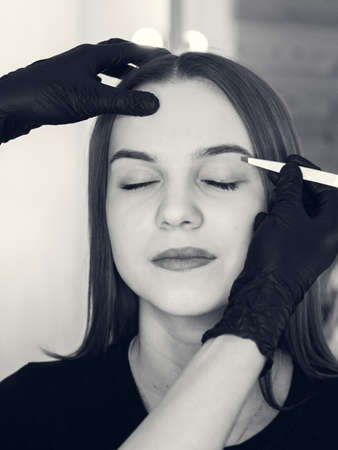 Artistic design of eyebrows. Correction. Pin forceps Woman having her eye brows tinted. Semi-permanent makeup for eyebrows. Focus on model's face and eyebrow