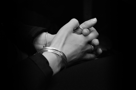 repentance: Woman hands clasped as in prayer. Tone black and white