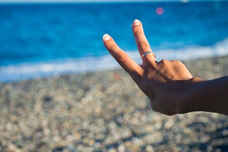 exult: two fingers with sea in the background: it can be a sign of victory or number two