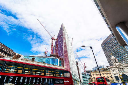periphery: London street with modern buildings and passage of the typical red double-decker bus
