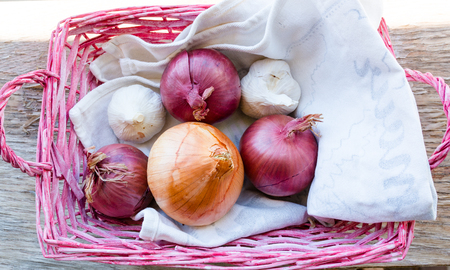 Cooking ingredients: onions and garlic in a pink basket Stock Photo