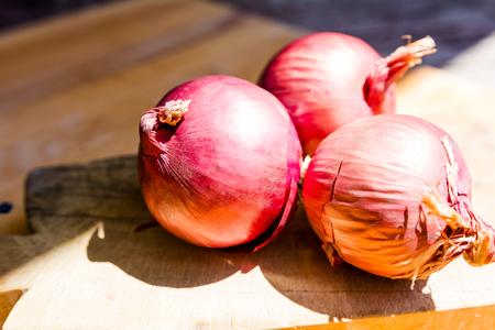 Three red onions on a cutting board