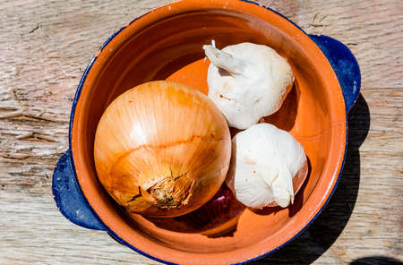 Onions and garlic in a bowl on wooden table