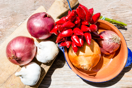 Cooking ingredients: garlic, onion and chili pepper on a wooden table